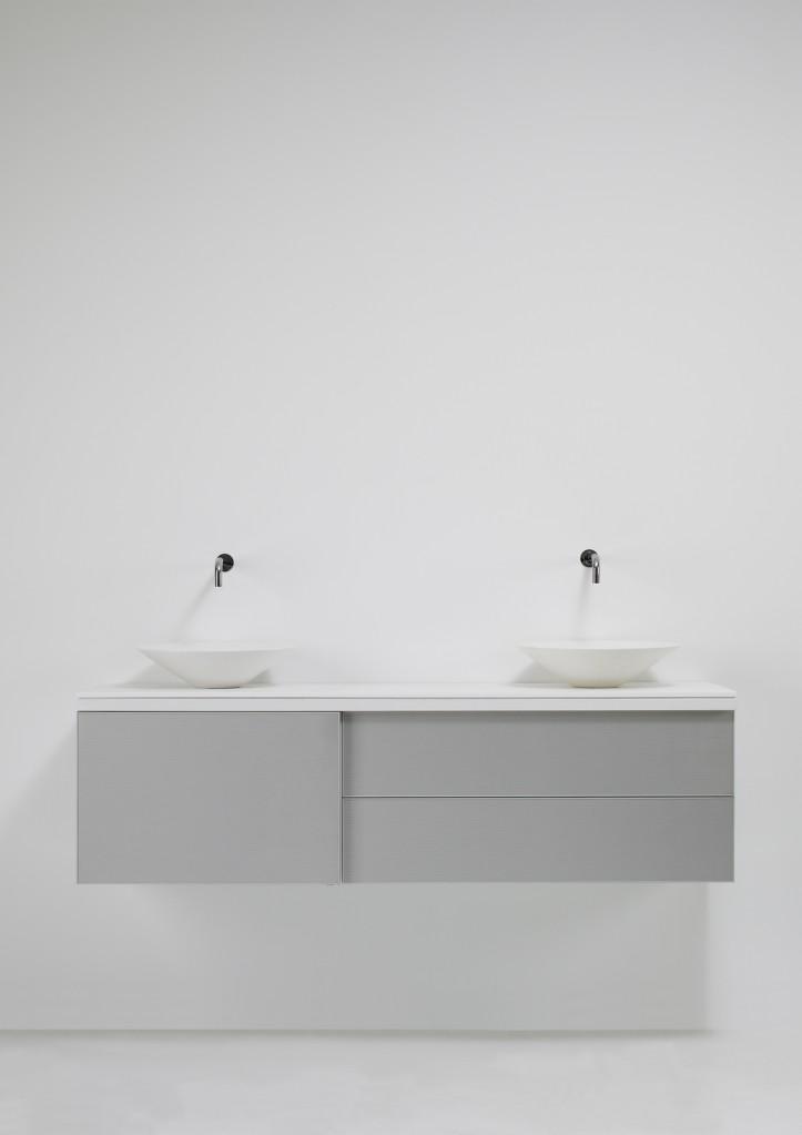 Módulo de la serie BAM, de ancho 150 x alto 44 x  profundidad 42.5 cm Estructura en laca brillo color blanco y puerta corredera y fronetras en aluminio. Encimera en Corian. Lavabos modelo CONO realizados también en Corian.
