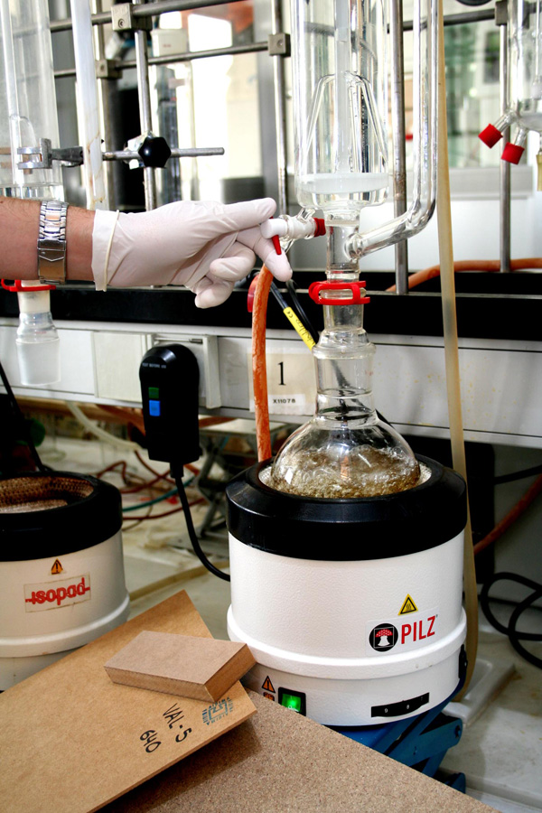 En este caso de la imagen se trata de determinación del contenido de formaldehído mediante extracción con tolueno en perforador, al que acompañan unas muestras ilustrativas de tableros.